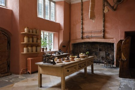 The sixteenth century kitchen built by Sir Richard Grenville at Buckland Abbey, Yelverton, Devon. The kitchen was re-sited to be near to the Great Hall and the room is dominated by two open hearths used for cooking. The walls are painted in a traditional pink limewash.