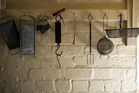 Old kitchen equipment including graters, a corkscrew, a toasting fork and a sieve at Sunnycroft, Shropshire.