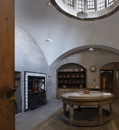 The Kitchen at Castle Drogo, Devon, with the circular beechwood table designed by the architect of the house, Edwin Lutyens. The only natural light in the room comes from the circular lantern window above the table, echoing its shape.