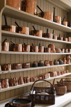 Part of the copper batterie de cuisine on the dresser shelves in the Kitchen at Attingham Park, Shropshire.