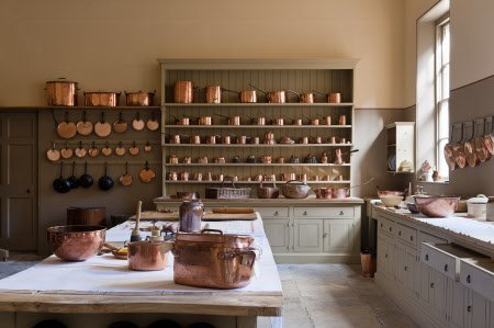 The Kitchen at Attingham Park, Shropshire. The elm-topped table and dresser are filled with the copper batterie de cuisine.