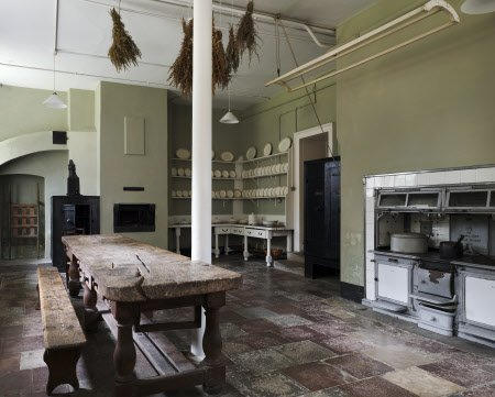 The Kitchen with wooden table, and range, at Osterley Park, Middlesex. The room has been a kitchen since the 1760s and is in the opposite corner of the house to the Eating Room, so that no noise or cooking odours should disturb the diners.