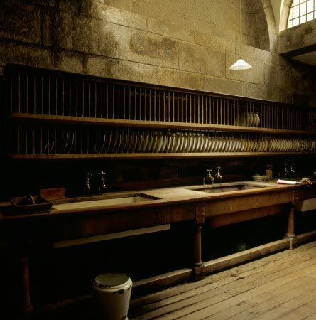 Three large oak-framed sinks and the long rows of plate racks above partially lit in the Scullery at Castle Drogo.
