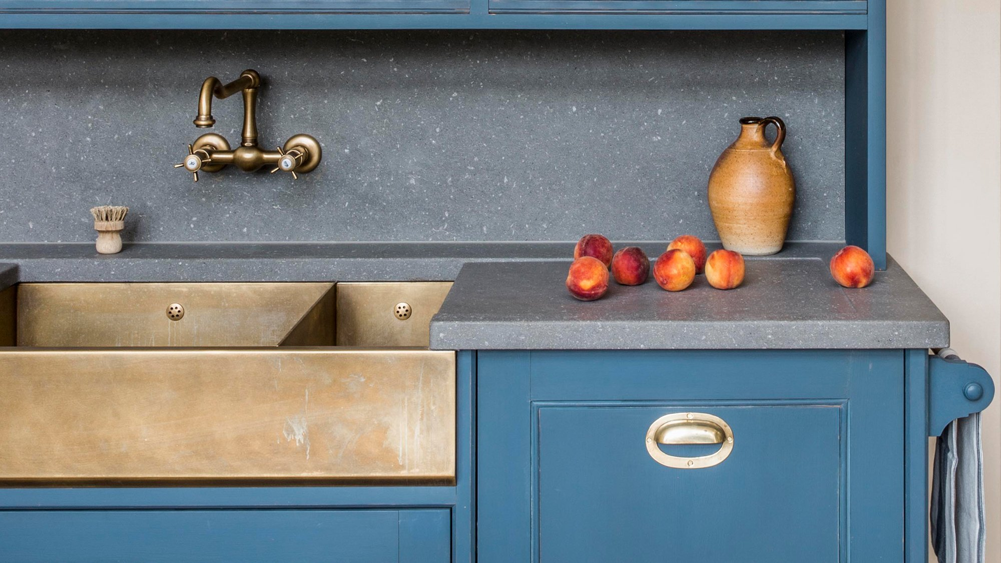 Aged brass sink and tap framed by a Basalt work surface
