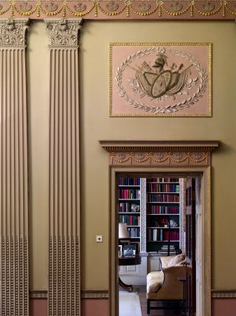 A view from the Hall to the Library at Basildon Park, Berkshire. The Neo-classical plasterwork decoration of the Hall shows the Adam influence on John Carr of York who designed the house in the late eighteenth century. The trophies of arms in panels above the doors are a reminder that entrance halls were used as armouries in earlier times. The Library bookcases are visble through the open door.