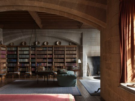 The Library at Castle Drogo, Devon. Edwin Lutyens was the architect of Drogo between 1910 and 1930 and he designed the oak bookcases. The lustre dishes above the bookcases are Hispano-Moresque and date from the 1700s.