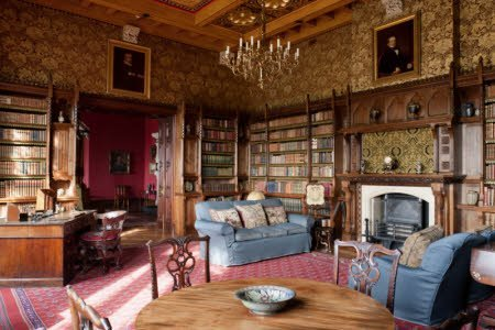 The Library at Knightshayes Court, Devon. The bookcases are in a Gothic style with linenfold panelling by John Crace.