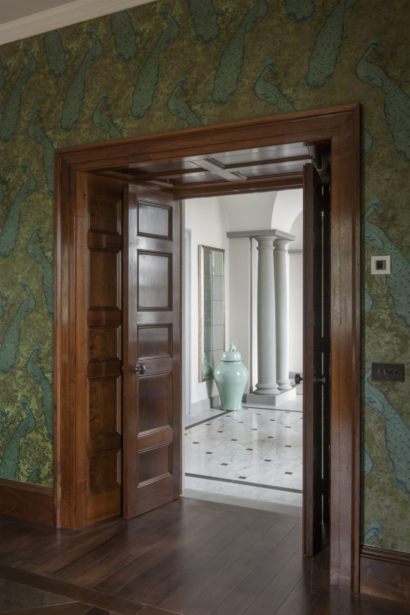 A view through a pair of double doors through to a grand hallway